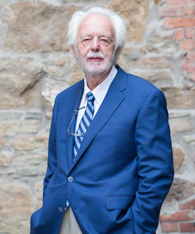 man with white hair and beard wearing blue suit and striped tie in front of stone wall