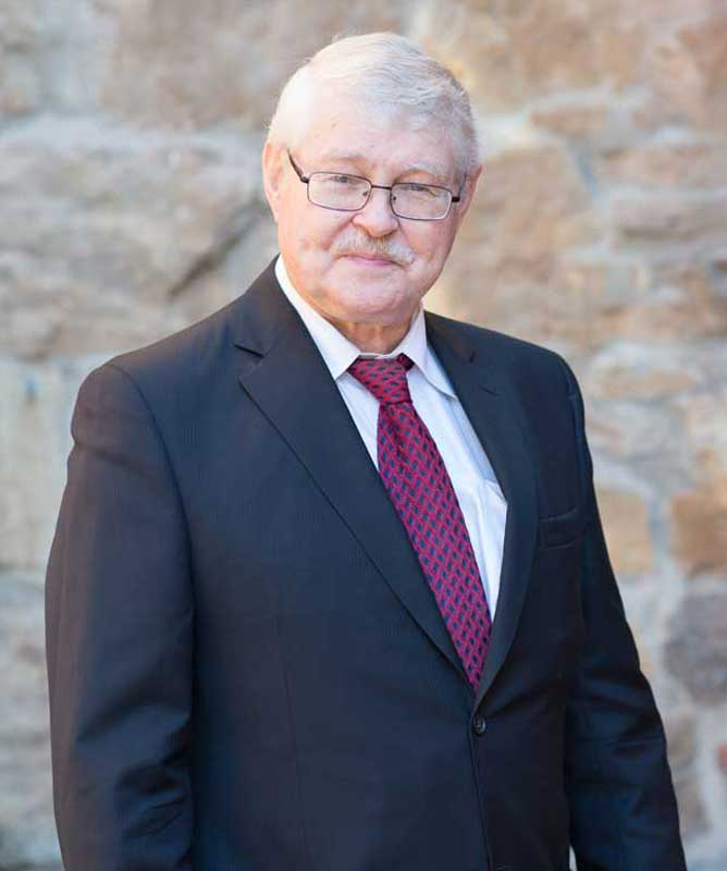 man with grey hair and moustache wearing glasses black suite and tie in front of stone wall