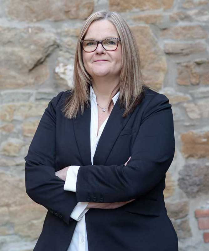 woman with long hair wearing glasses black blazer and white shirt in front of stone wall