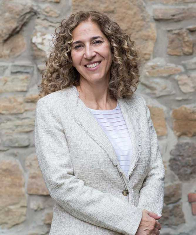 smiling woman with curly hair wearing light blazer and striped white shirt in front of stone wall